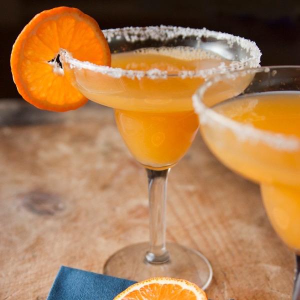 Mandarinos vodkazselé cukrozott szélű széles üvegpoharakba töltve, a pohár szélén egy mandarinszelettel.