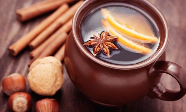 Kínai csillagánizsból készült tea citromszeletekkel egy barna csuporban, mellette fahéjrudak, dió és mogyoró.