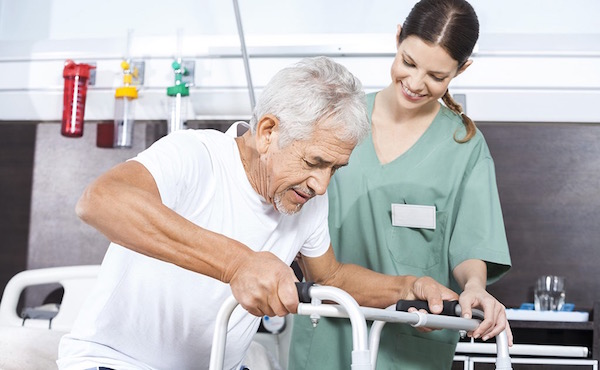 Stroke-os beteg ágyból való felállítása járókerettel egy fizioterapeuta segítségével.