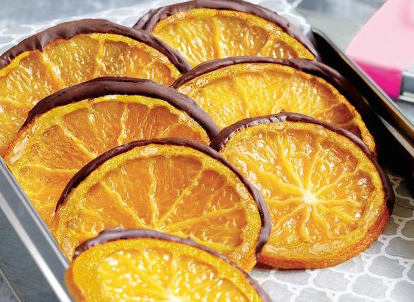 Kandírozott narancsszeletek, melyeknek a pereme csokoládéba van mártva.
