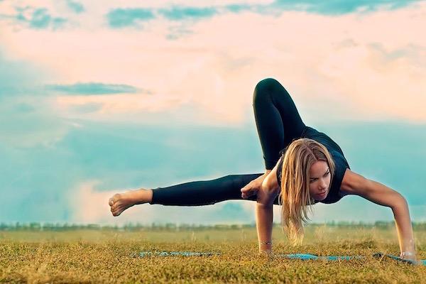 Fekete ruhában jógázó nő a mezőn kitartott ászanát végez.
