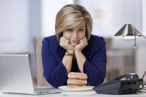 Kék blézerben ül az irodájában állát megtámasztva egy hölgy, előtte egy kistányéron három fánk.
