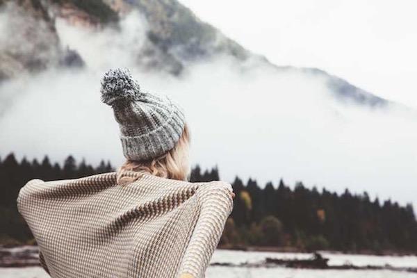 Sapkában áll háttal a kamerának egy fiatal lány, hátán egy vastag takaró, a háttérben egy nagy hegy, melyet beborít a köd.
