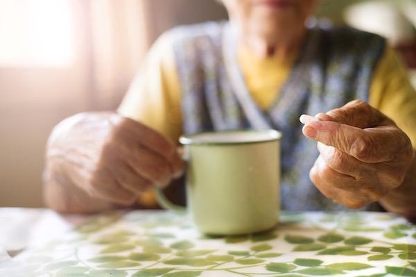 Idős néni a konyhaasztalánál ülve egy szem tablettát vesz be.