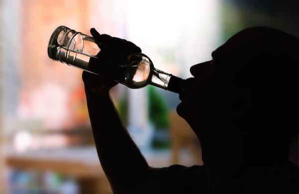 Üvegből ivó alkoholista árnyképe.
