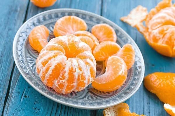Megpucolt mandarin egészben és gerezdekre bontva egy kistányéron.