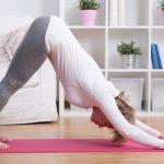 Idősebb nő jógagyakorlatot végez a nappali szobájában egy pink színű jógamatracon.