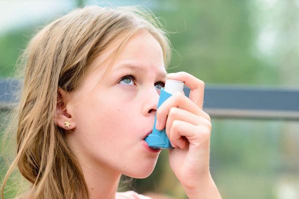 Kislány szájában kék színű spray asztma ellen.