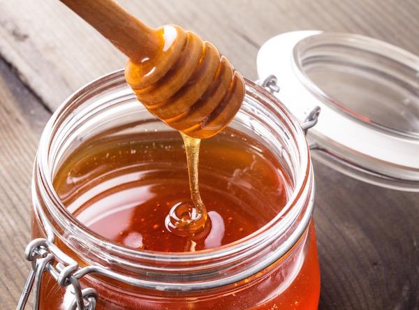 Csatos tetejű üvegben lévő mézben egy mézkanál.