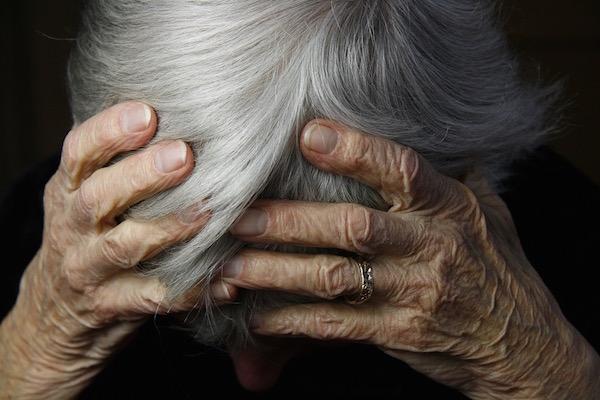 Idős, ősz hajú néni lehajtott fejét fogja két kezével.