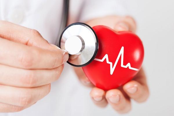 """Egy orvos sztetoszkópjával """"vizsgál"""" egy piros műanyag szívet."""