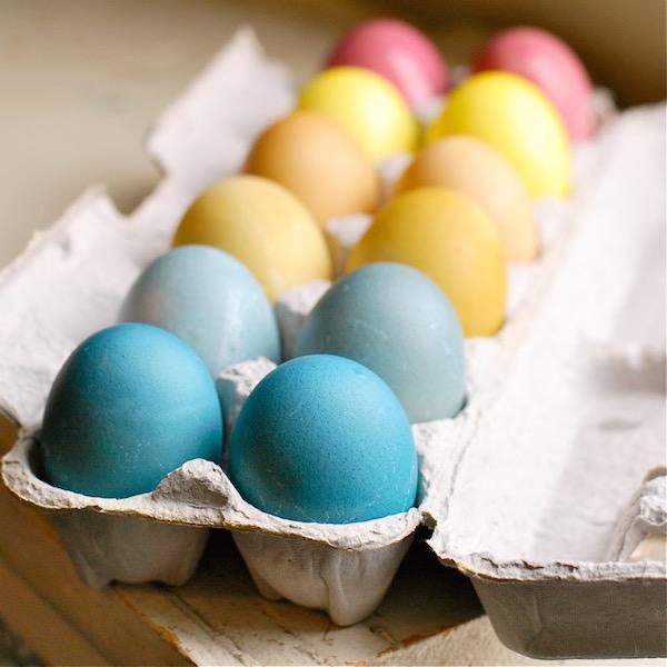 Természetes módon megfestett húsvéti tojások szép pasztellszínekben egy tojástartóba téve.