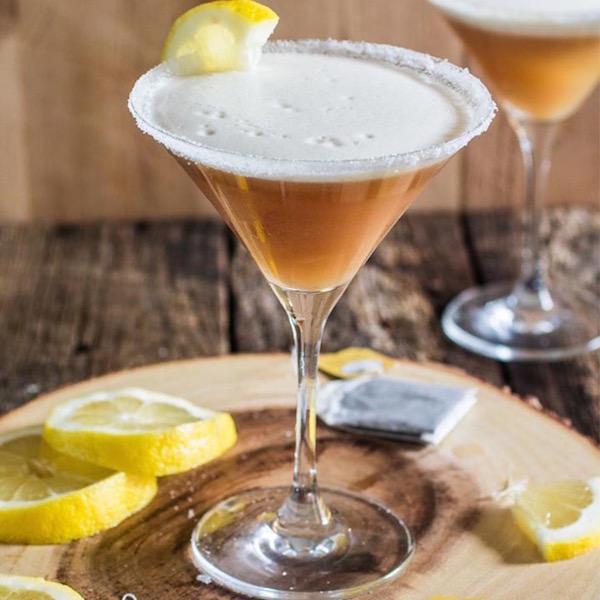 Earl Grey teát tartalmazó koktél szép pohárkában, mellette citromkarikák és teafilter.