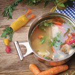 Frissen készült húsleves fazékban, mellette sárgarépa és friss fűszernövények.
