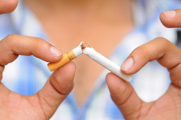 Egy hölgy kettétör kezében egy cigarettát.