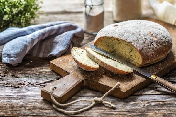 Teljes kiőrlésű lisztből készült medvehagymás kenyér egy vágódeszkán.