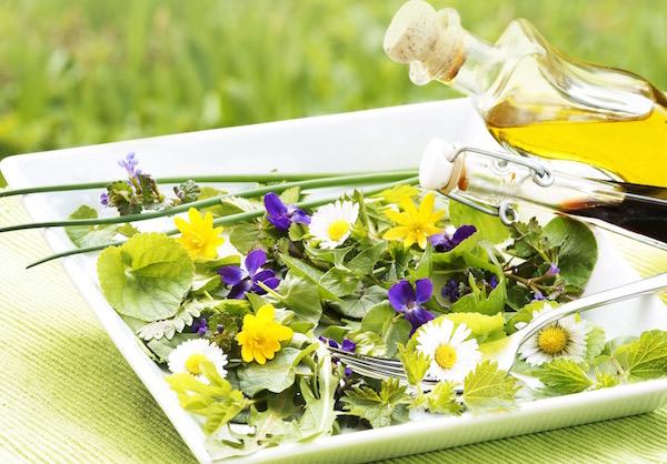 Tavaszi gyógynövények és ehető virágok egy salátástálon, mellette egy villa és olívaolaj.