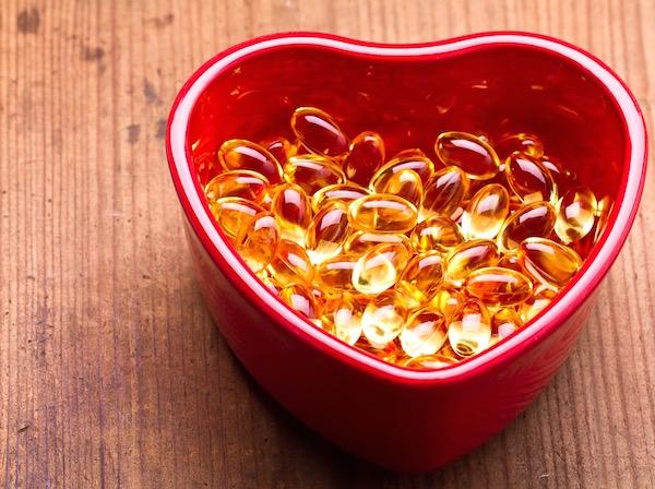 Egy szív alakú piros tál tele E-vitaminnal.