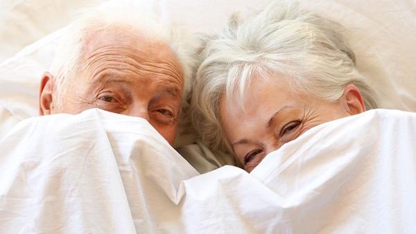 Idős házaspár az ágyban mosolyogva, akik a takarót magukra húzzák.