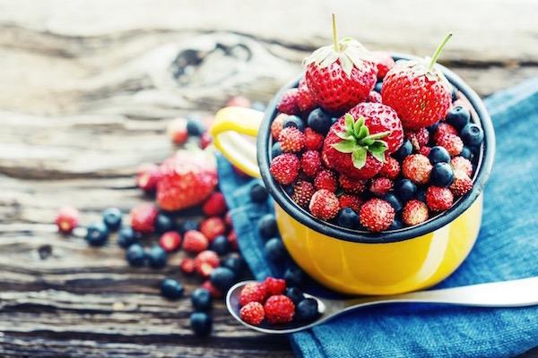 Citromsárga füles edénykében sok-sok pirso bogyós gyümölcs: málna, eper, szamóca és áfonya.