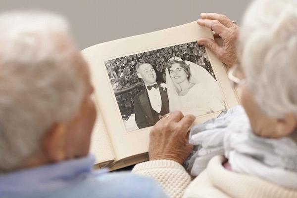 Régi esküvői fényképalbumát nézegeti egy idős házaspár.
