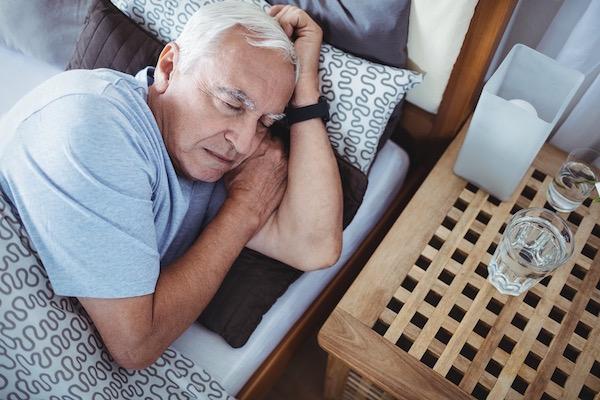 Idős ember otthon a hálószobájában alszik.