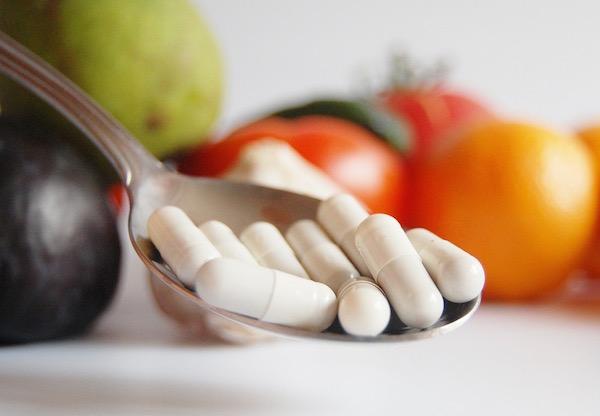 Vitaminkapszulákat tartalmazó nagykanál sok zöldség és gyümölcs előtt.