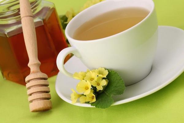 Kankalinból készült gyógytea fehér csészében, mellette mézkanál és mézes csupor.