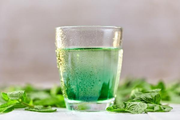 Klorofillt tartalmazó ital, mellette zöld levelek.