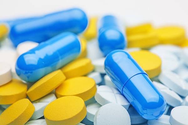 Három különböző színű és formájú vitamin étrend-kiegészítőként.