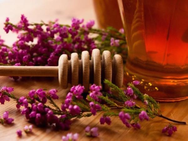 Csarab lila virágai, mellette a belőlük készült hangaméz és mézkanál.