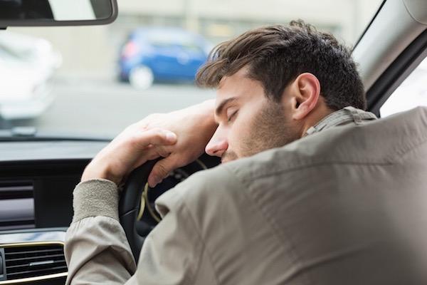 Fiatal férfi fáradtan ráborul az autó kormányára, még a szemét is behunyja.