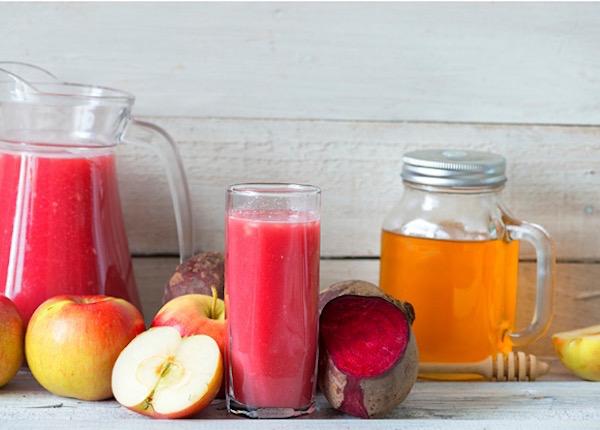 Alma, cékla, méz és a belőlük készült finom, egészséges ital kancsóban és pohárban.