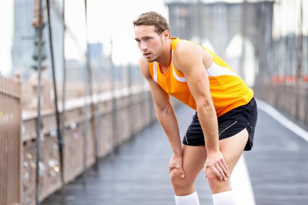 Fiatal férfi futás közben megáll pihenni egy hídon.