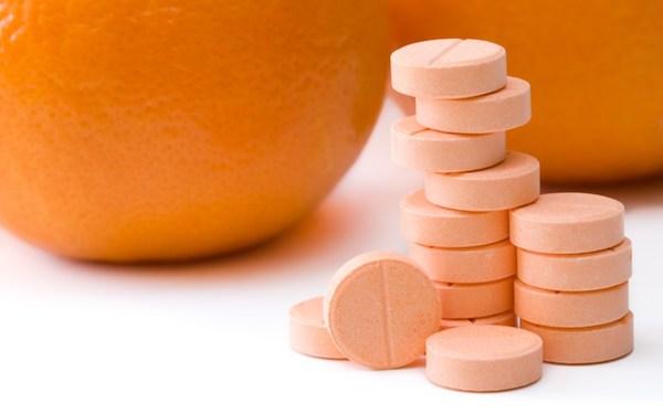 C-vitamint tartalmazó tabletták, a háttérben narancsok.