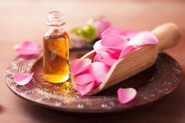 Egy díszes tányéron rózsaszirmok és rózsaolaj kis üvegben.