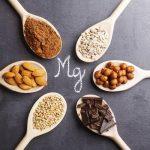 Magnéziumban gazdag élelmiszerek egymás mellett fakanalakon: csokoládé. mandula, mogyoró, kakaó, hajdina, bab.
