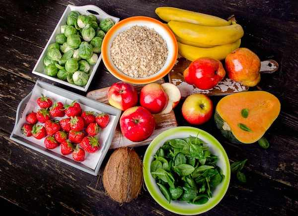 Magas rosttartalommal rendelkező élelmiszerek egymás mellett: banán, alma, eper, kelbimbó, kókuszdió, spenót, gabonapehely, sütőtök.