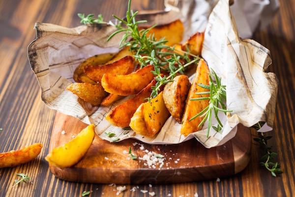 Sült krumpli tengeri sóval és friss fűszernövényágakkal.
