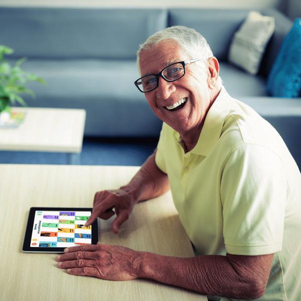 Kirakóst vagy memóriajátékot játszik az iPadjén egy idősebb férfi.
