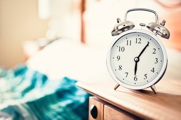 Hálószobában az ágy melletti éjjeliszekrényen 6.05-öt mutat az ébresztőóra.