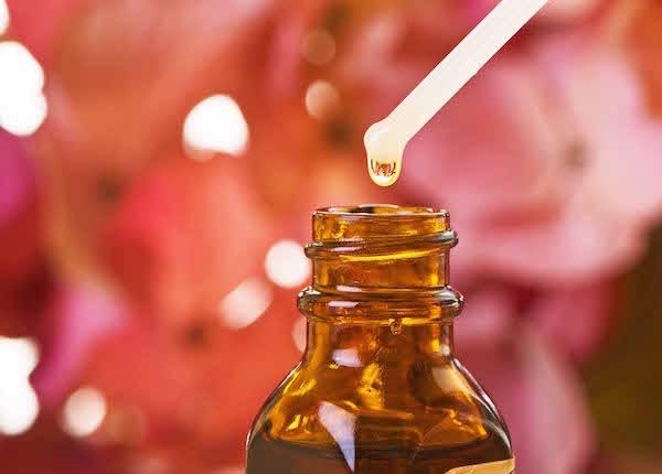 Virágesszencia egy pipettáról lecsöppentve az üvegbe, a háttérben elmosódva egy csokor rózsa.