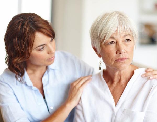 Alzheimer-kórban szenvedő hölgy vállát fogja a lánya.
