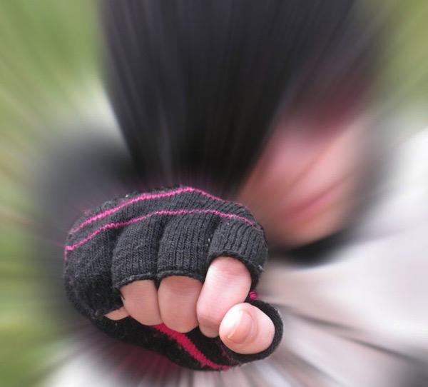 Egy fiú ütésre emeli öklét, az arca elmosódik, az öklén van a hangsúly.