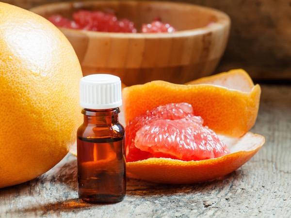 Grépfrút egészben és cikkekre bontva, mellette a gyümölcs esszenciális olaja.