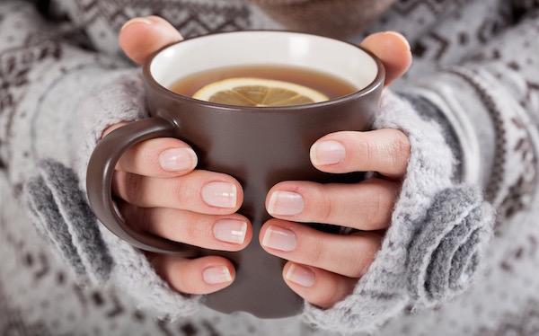 Citromos gyógytea barna bögrében egy szürke pulóveres hölgy kezében.