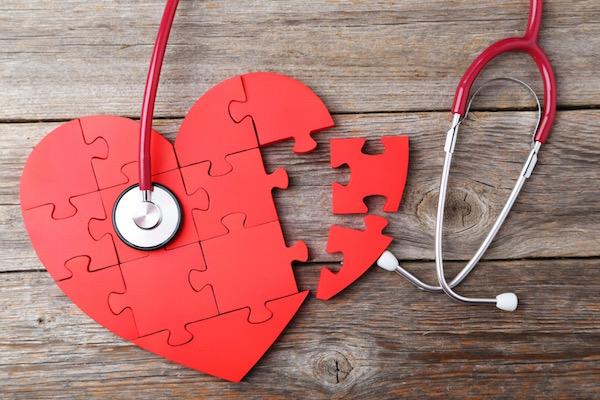 Piros szív puzzle elemekből kirakva, mellette egy piros fonendoszkóp.