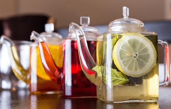 Különféle színű gyógynövényteák átlátszó üvegkancsókban egymás mellett.