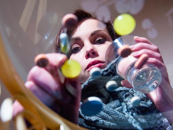 Üvegasztalról vesz el vitaminokat egy pohár víz kíséretében egy ötvenes hölgy.