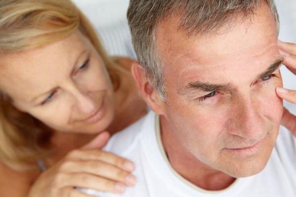 Idősebb férfi vállát átfogja a felesége.